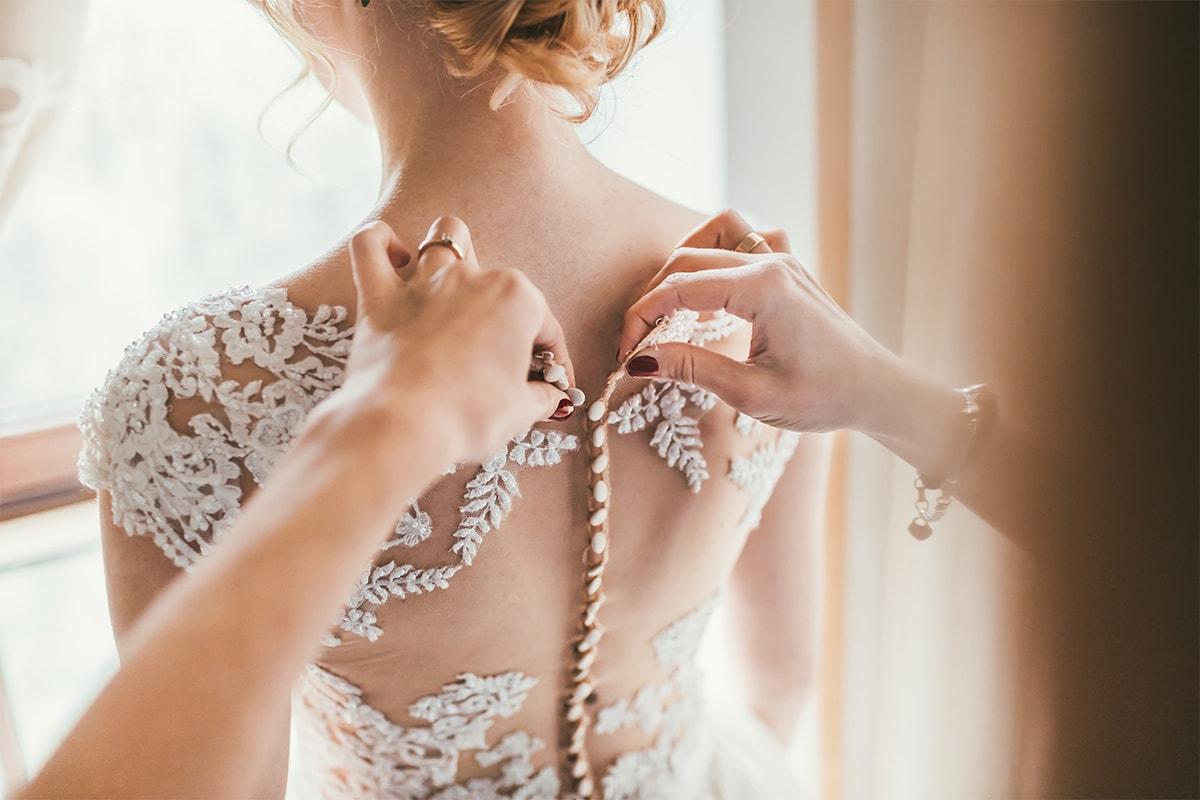 ウェディングドレスを着付けしてもらう女性の後ろ姿
